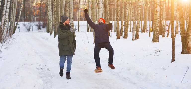Two young modern man while walking through a birch forest in winter. One of them slipped and lost his balance, his friend held out his arms. Freeze frame before falling into the snow.