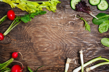 Spring vegetables on wooden background with copy space. Radish, cucumber, green salad, celery and green onion - fresh harvest from the garden.