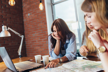Female office workers planning vacation using map