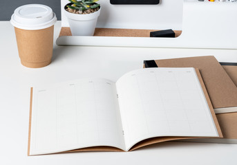 top view of open calendar planner with modern office stationery and take away coffee cup on white desk in office.mock up space of organizer table notebook.