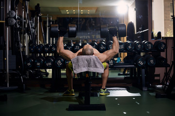 """one young man - bodybuilder, exercise """"Two Arm Dumbbell Bench Press"""", in gym. Row of dumbbells - fitness equipment."""