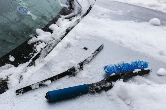 damaged windshield wiper and blue brush lying on a snowy car hood