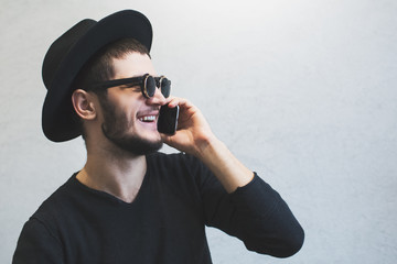 Profile portrait of laughing young guy who using smartphone over white background. Wearing sunglasses and hat, dressed in black.