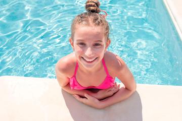 Teen girl in swimming pool squinting her eyes