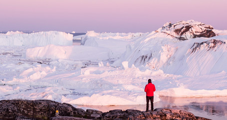 Travel in arctic landscape nature with icebergs - Greenland tourist man explorer