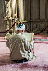 Old man reading Quran in a mosque