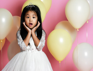surprised kid girl with balloons in princess dress with tiara