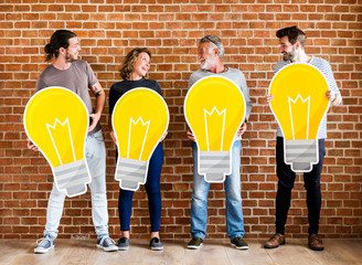 Diverse people holding light bulb icons Wall mural