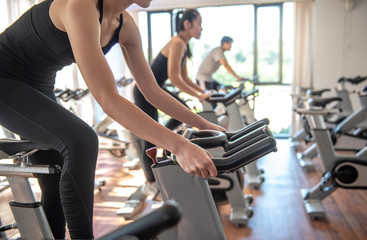 Select focus of hands  young woman doing workout biking on Indoor cycling  gym bike. Girl cyclist working out interval training on bicycle. - Image
