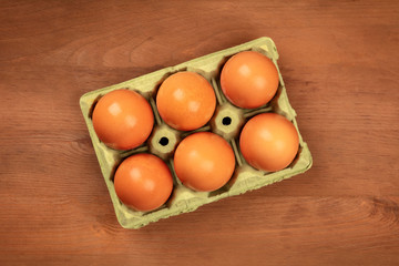 A photo of eggs in a carton, shot from the top on a dark rustic background with copy space