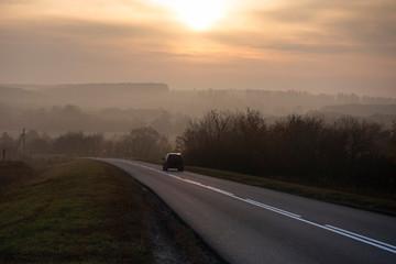Car traveling on the asphalt road in a rural autumn landscape at sunset