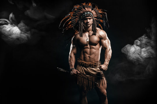 American Indian Apache warrior chief  in traditional clothing and feathered headdress with weapon. Indian chieftain of the tribe with muscled strength body with arrows.