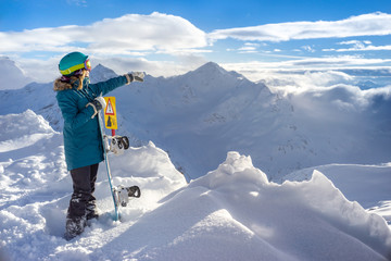 Poster Glisse hiver Happy young woman snowboarder shows towards the snowy high mountains and beautiful scenery on the slopes of the ski resort. Holds a snowboard in one hand