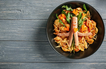 Plate with pasta and sausage for child on wooden table