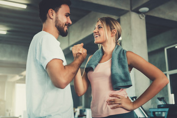 Attractive young couple handshaking after workout in fitness gym., Portrait of man and woman couple...
