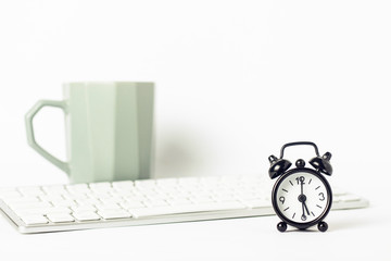 Black alarm clock, a cup of coffee or tea and a keyboard on a white background. Office concept, computer work, work day, hourly pay.