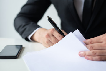 Closeup of business man signing document at office desk. Entrepreneur wearing suit and working. Contract concept. Cropped front view.