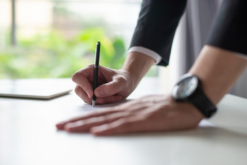 Closeup of business man writing on sheet of paper at desk. Entrepreneur standing and working at office desk with window and blurred green view in background. Office work concept. Cropped side view.