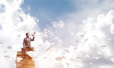 Businessman announcing something in loudspeaker and paper planes fly around