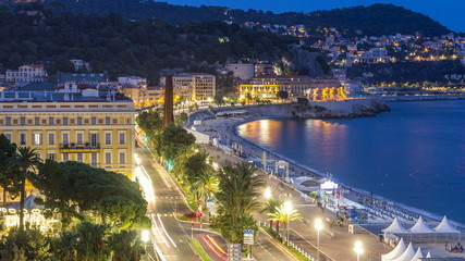 Evening aerial panorama of Nice day to night timelapse, France. Lighted Old Town little streets and waterfront after sunset