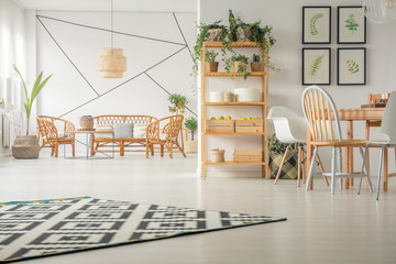 Patterned carpet on white wooden floor in trendy living and dining room interior with rattan sofa and armchairs
