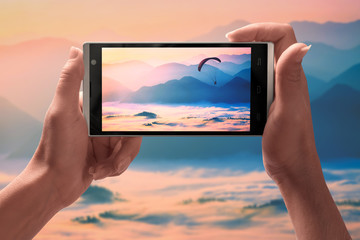 Paraglider flying over the mountains on a screen of smartphone