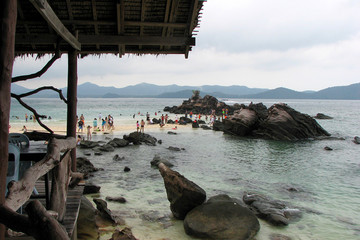 People walk in the sea near the coast surrounded by huge stones against the backdrop of the mountains, Thailand.