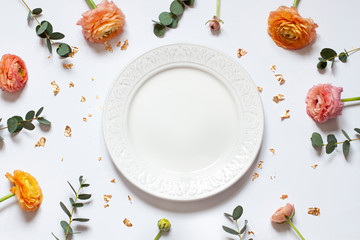 Empty plate concept flat lay with floral decorations on the white backdround. Top view Valentines day, Mothers day or Easter card. Copy space