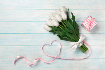 A bouquet of white tulips and a pink ribbon in the form of a heart with a gift box on blue wooden boards . Mother's day