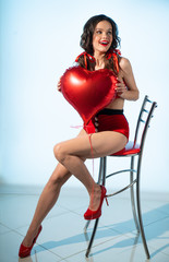A girl who looks like a doll with a red inflatable heart