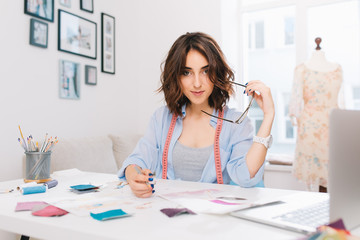 A brunette girl is sitting at the table in the workshop.  She has blue shirt and creative mess on the table. She holds glasses and pencil in hands and  looking  to the camera.