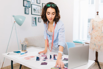 A brunette girl in a gray dress and blue shirt is standing near the table in a workshop studio. She has a lot of creative stuff  on the table. She is looking for some material samples.