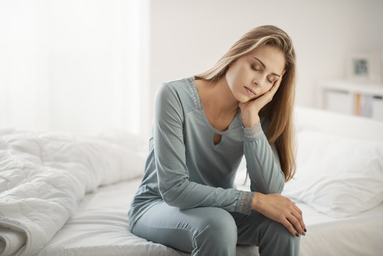 Exhausted woman sitting on bed