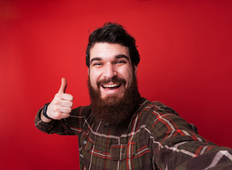 Cheerful man with beard taking selfie over red background and showing thumbs up