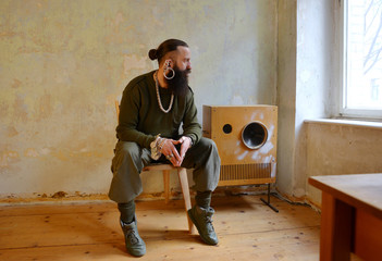 a bearded men sitting in a room with a big loudspeaker