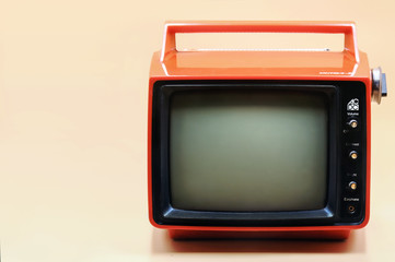 Red retro television on peach color background