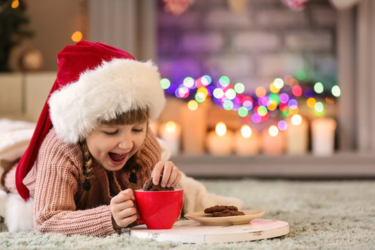 Cute little girl in Santa hat drinking hot chocolate and eating cookies at home on Christmas eve
