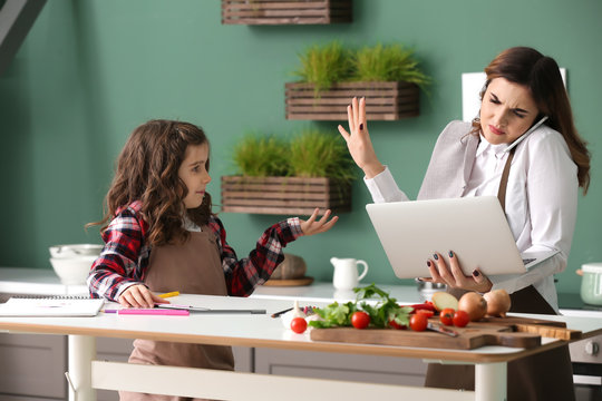 Stressed busy mother with daughter working in kitchen at home