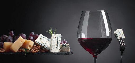 Glass of red wine with various cheeses, grapes, walnuts and rosemary.