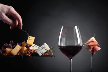 Glass of red wine with various cheeses , fruits and prosciutto.