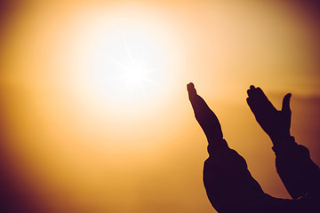 Silhouette of man praying at the top mountain with abstract sun cross ray god power