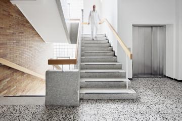 Krankenhaus mit Treppe und Aufzug mit Arzt und Bewegungsunschärfe hinunter laufen Fototapete