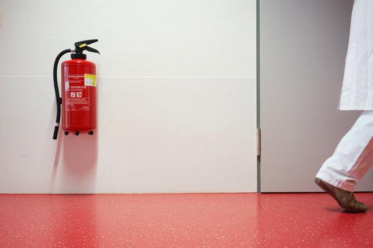 Krankenhaus mit Korridor Feuerlöscher und Frau unscharf in Zentralperspektive