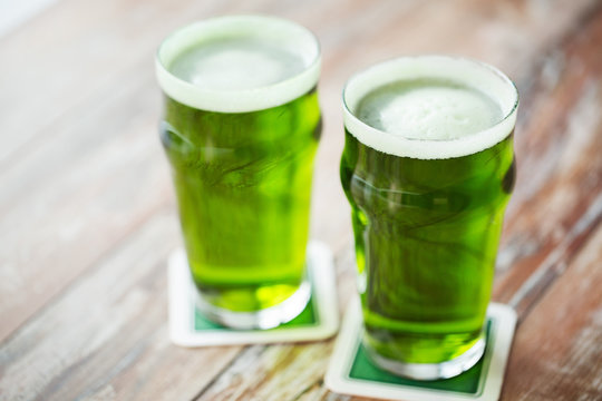 st patricks day, holidays and celebration concept - two glasses of green beer on wooden table