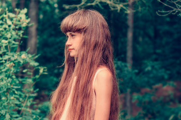 young girl with long hair and fringe, with natural makeup looks to the side against the background of the forest