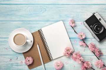 White cup cappuccino with sakura flowers, notebook and old photo camera on a blue wooden table