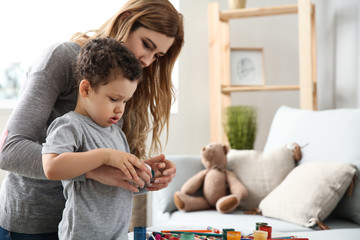 Cute little boy with mother drawing at home
