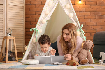 Young mother with cute little son reading book in hovel at home Wall mural