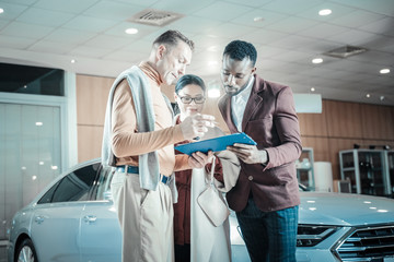 Man wearing beige trousers signing documents for insurance of car
