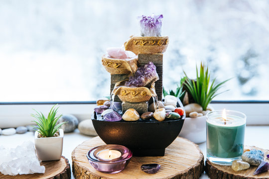 Relaxing spiritual Feng Shui altar set with nature, water and fire element. Tabletop small electrical fountain with water pouring cups. Symbol of wealth and prosperity.